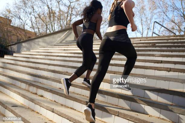 two sportswomen during workout on stairs - leggings stock pictures, royalty-free photos & images