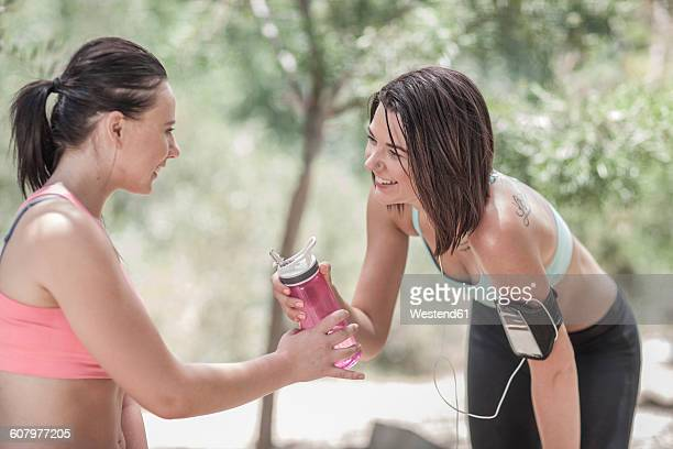 Two sportswomen sharing water after running
