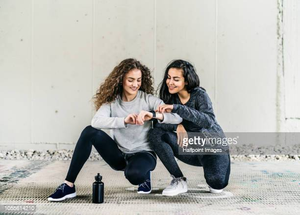 Two sporty female friends with water bottle using smart watch outdoors in the city.