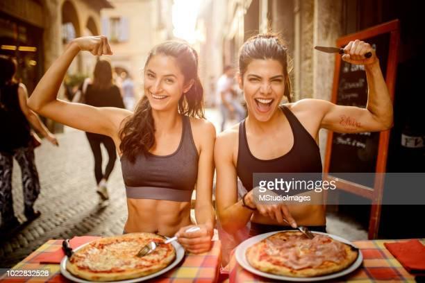 two sporty woman eating pizza. - forza italia foto e immagini stock