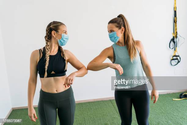 two sporty women wearing face masks giving elbow bump at health club - face guard sport stock pictures, royalty-free photos & images