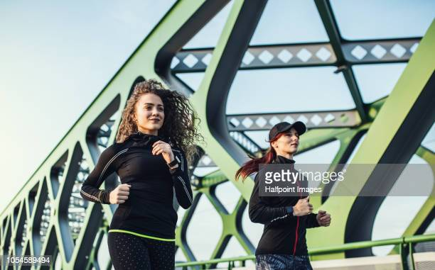 Two sporty young women running on the bridge outdoors in the city.