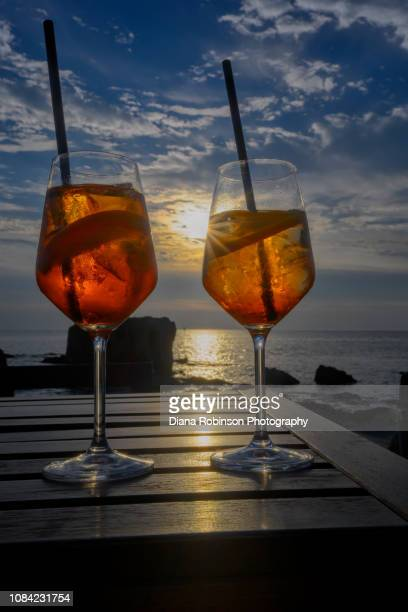 Two Aperol Spritz drinks at sunset in the coastal town of Alghero, Sardinia, Italy