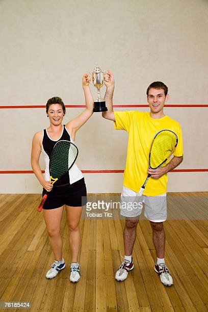 Two squash team mates holding a trophy