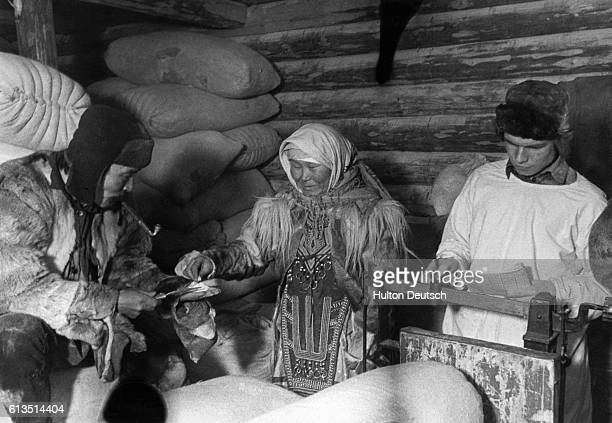 Two squirrel hunters from the Kyasnoyarsk region of Siberia buy flour at a rustic supply store