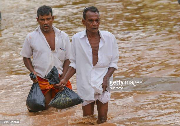 Two Sri Lankan men walk across a road inundated by floods at Kaduwela 20kms away from capital city Colombo Sri Lanka Friday 26th May 2017 More than...
