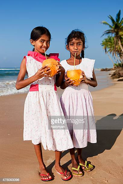 Two Sri Lankan young girls drinking coconut milk on beach