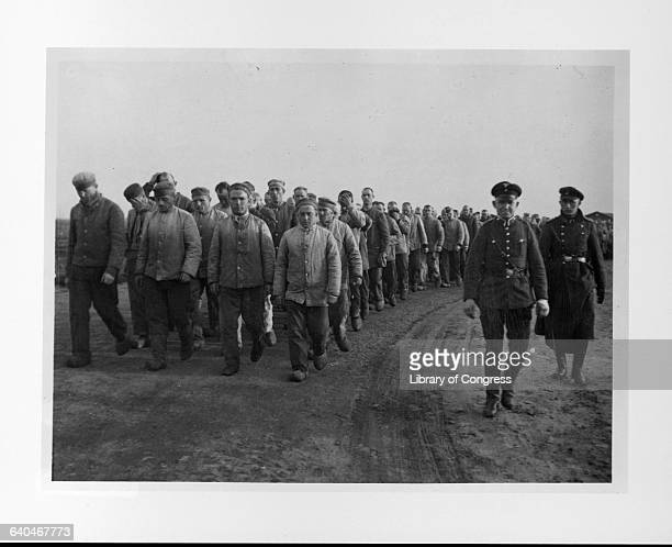 Two SS guards march a crowd of prisoners at a concentration camp at Emsland, Germany. 1935. | Location: Emsland, Germany.