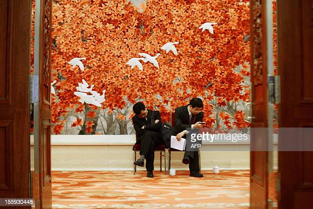 Two staff members of the Great Hall of the People take their seats during the 18th National Congress of the Communist Party of China in Beijing on...