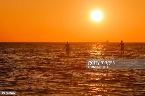TOPSHOT Two stand up paddle boarders are seen on the Baltic Sea as sun rises over Kiel northern Germany on May 24 2018 / Germany OUT