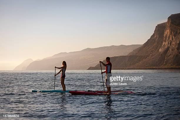 two stand up paddle boarders on misty morning - paddleboard stock photos and pictures