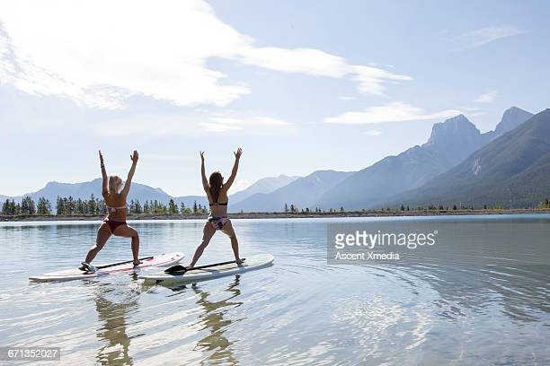 two stand up paddleboard ladies perform yoga moves - paddleboard stock photos and pictures