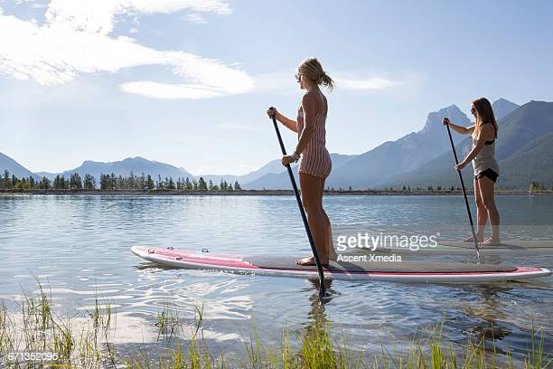 two stand up paddleboard ladies pilot mtn lake - paddleboard stock photos and pictures