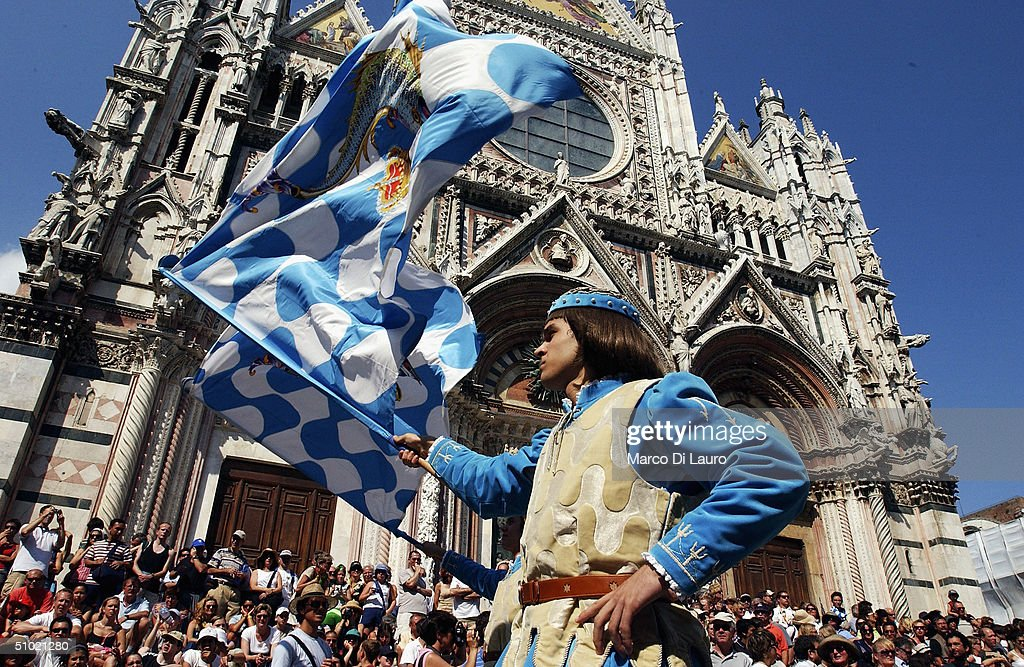 Two standard bearer belonging to the Onda (Wave) one of the seventeen contrade, performs the flag waving display in front of the Cathedral of Siena before the Palio horse race, on July 2, 2004 in Siena, Italy. The city's 17 separate Contrade or neighbourhoods vie to compete in the prestigious Palio race, which takes place at the end of a week of festivities which encourage huge support and fierce competition between the participants.