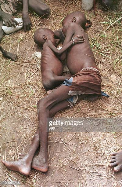 Two starving boys cling to each other outside a feeding centre 09 August in the village of Acumcum in the Bahr El Ghazal Province of southern Sudan...