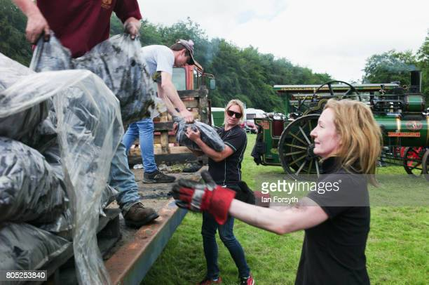 Two steam engine drivers help to unload coal for the engines during the Duncombe Park Steam Rally on July 1 2017 in Helmsley United Kingdom Held...