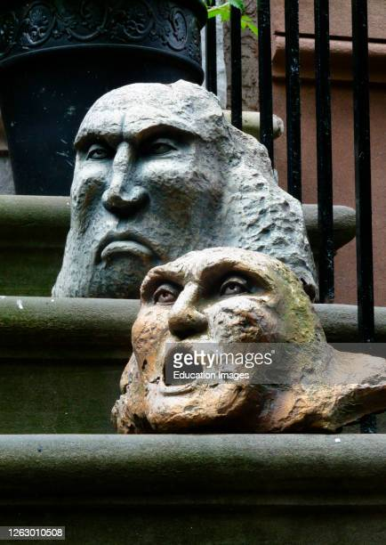 Two stone face sculptures on brownstone steps, Gramercy Park, New York City.