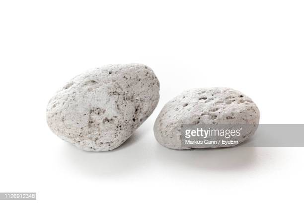 two stones against white background - pietra roccia foto e immagini stock