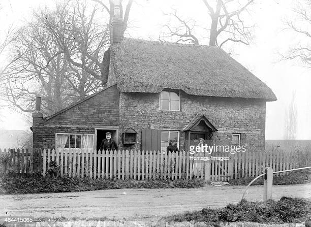 Two storey brick built cottage with a thatched roof, showing the inhabitants standing outside in the garden, Uffington, Oxfordshire, 1916.