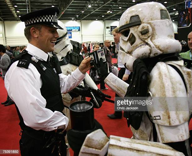 Two storm troopers check a policeman's ID at the Star Wars Celebration Europe in the Excel centre on July 13 2007 in London England The celebration...