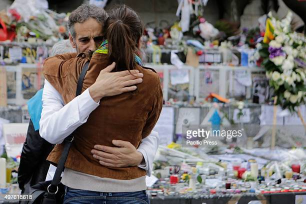 Two strangers hug at the memorial for the people killed during the Paris attacks at the Place de la Republique Parisians and tourists continue to...
