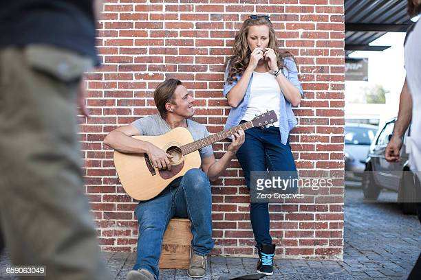 Two street musicians playing together, entertaining pedestrians