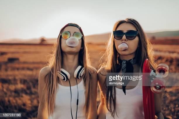 dos chicas adolescentes de estilo callejero haciendo globos de goma de mascar - música pop fotografías e imágenes de stock