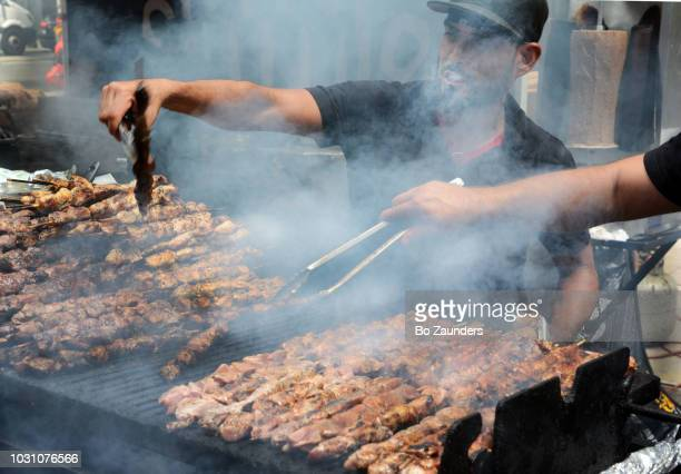 Two street vendors preparing barbecued chicken at a Midtown Manhattan street fair.