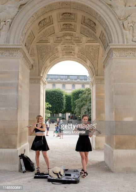 Two streets artists performs under the Arc de Triomphe du Carrousel on August 28 2019 The triumphal arch of the Carrousel is a Parisian monument...