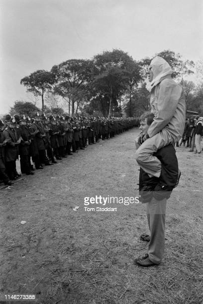 Two striking miners on atop the shoulders of the other stand in front of a line of police officers near the Orgreave coking plant Orgreave Yorkshire...