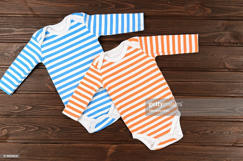 Two striped baby bodysuits on wooden background : Stock Photo