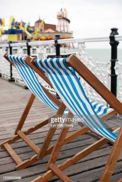 two striped empty deckchairs on brighton pier - lyn holly coorg stock pictures, royalty-free photos & images