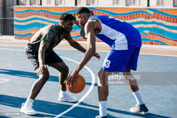 Two strong players facing off on basketball cort