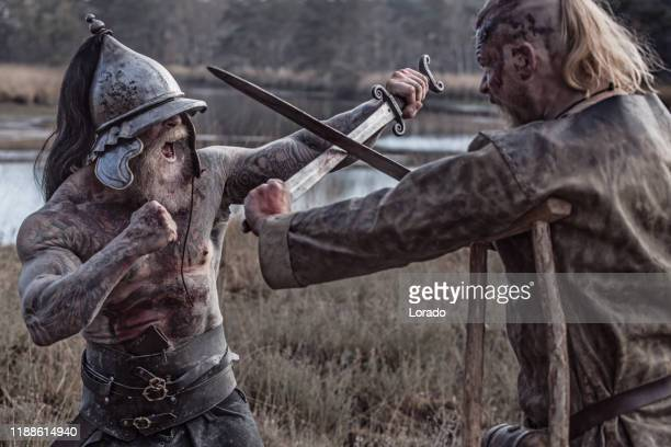 two strong viking men fighting in hand to hand combat - battle stock pictures, royalty-free photos & images