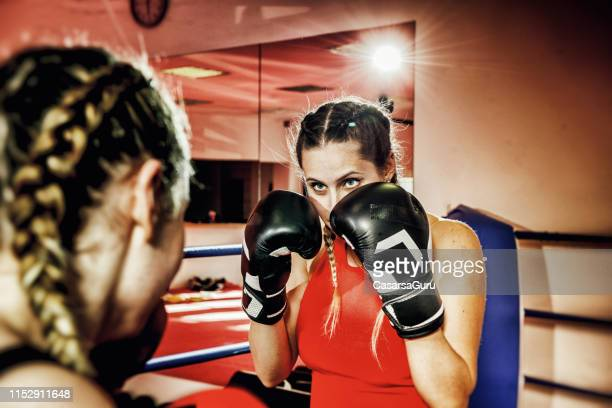 two strong women sparing in a boxing ring - women's boxing stock pictures, royalty-free photos & images