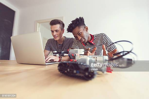 Two studens programming a robot