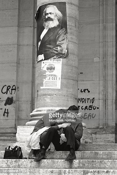 Two students are embraced on the stairs at the entrance to the Sorbonne under a column of the facade where are standing out a portrait of Karl Marx...