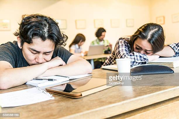 Two students asleep in class after hours of studies