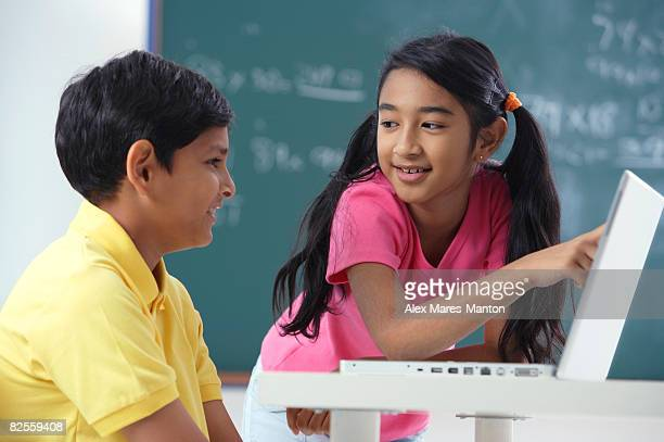 two students at laptop, girl pointing to screen