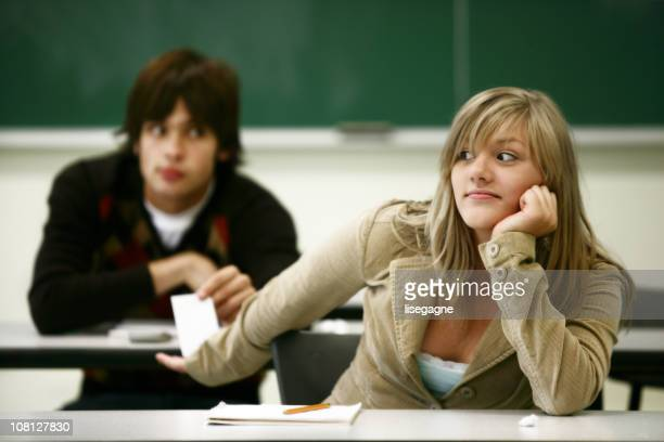 Zwei Studenten, die Austausch von Notizen in Class