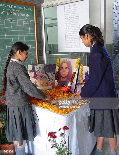 Two students from the Tagore Baal Niketan School arrange marigold flowers on the photograph of astronaut Kalpana Chawla in Karnal 130 kilometers from...