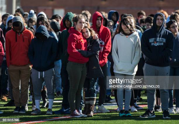 TOPSHOT Two students from WashingtonLee High School hug as other students look on in a memorial service during a walk out in Arlington Virginia on...