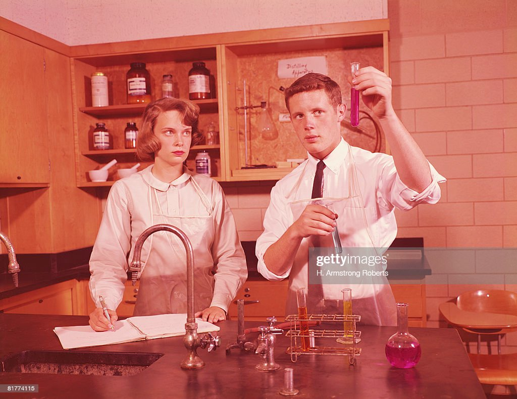 Two students in chemistry laboratory, conducting experiment, boy holding test-tube, girl making notes. : Stock-Foto