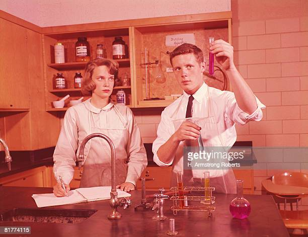 Two students in chemistry laboratory, conducting experiment, boy holding test-tube, girl making notes.