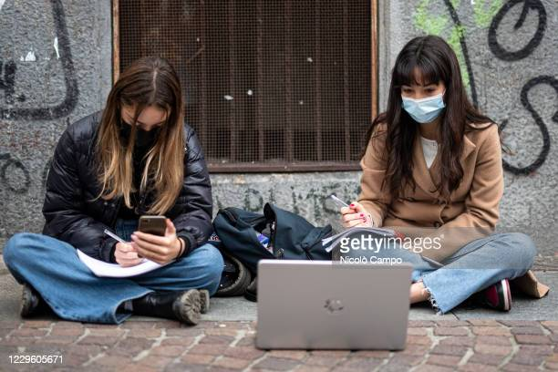 Two students of high school Gioberti follow a distance learning lesson on the street outside their school to protest against schools closures imposed...