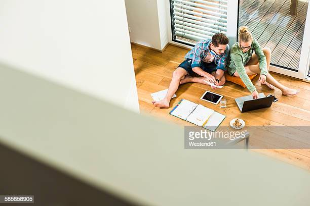 Two students sitting on wooden floor learning
