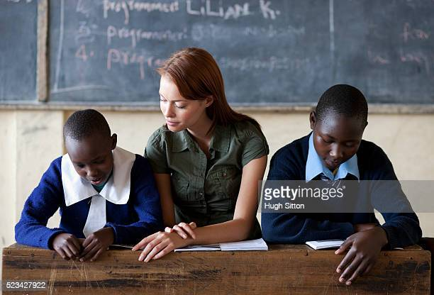 two students sitting with teacher reading in classroom, kenya - hugh sitton stock pictures, royalty-free photos & images