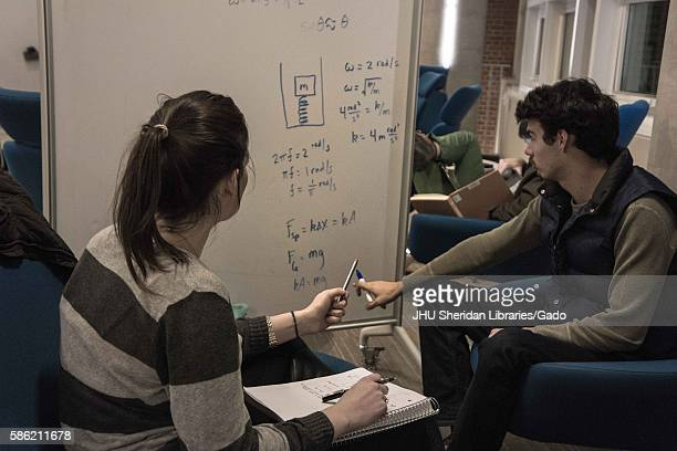 Two students study using a whiteboard in the Brody Learning Commons, a library and study space on the Homewood campus of the Johns Hopkins University...