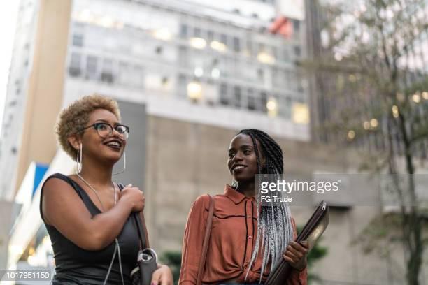 twee studenten praten op straat - braziliaanse etniciteit stockfoto's en -beelden
