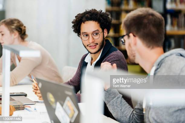 two students talking to each other while studying in library - 20 29 years stock pictures, royalty-free photos & images
